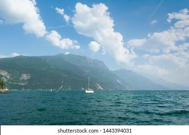 Beautiful view of Lago Di Garda coastline with sailing boat on the foreground. Riva Del Garda, Italy.