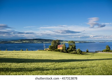 Beautiful view of lake Mjosa with yellow house and the green  field in summer in sunset with blue sky. Mjosa lake, Norway.