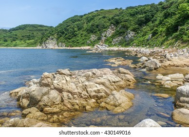 Beautiful view of land and sea. Hills are covered with green forests, blue sky, rocks on the shore.