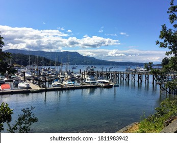 A beautiful view of a large marina full of boats in a large bay on a sunny day with the mountains in the background in Brentwood Bay, Vancouver Island, Canada.