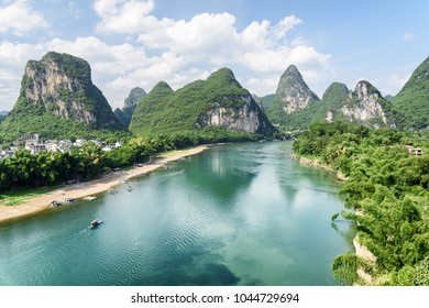 Beautiful view of the Li River (Lijiang River) with azure water among scenic karst mountains at Yangshuo County of Guilin, China. Amazing green hills on blue sky background. Summer sunny landscape.