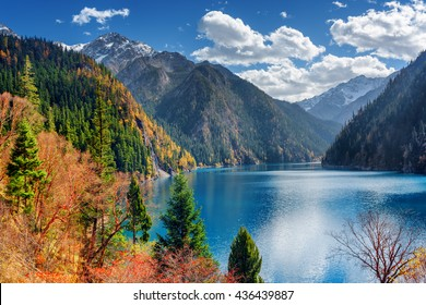 Beautiful view of the Long Lake among colorful fall woods and snow-capped mountains in Jiuzhaigou nature reserve (Jiuzhai Valley National Park), China. Amazing snowy peaks are visible in background.