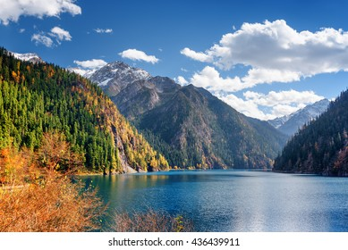 Beautiful view of the Long Lake among colorful fall woods and mountains in Jiuzhaigou nature reserve (Jiuzhai Valley National Park), China. Scenic snowy peaks and blue sky are visible in background.