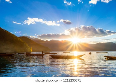 Beautiful view of LuGu Lake, at sunset in summer, wooden ships calmly on the lake, illuminated by the sun, in Yunnan Province, China