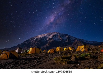 Beautiful view of the milky way over mount Kilimanjaro, Tanzania with many tents at the base camp. Millions of stars in the night African sky.