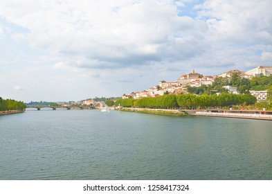Beautiful view of Mondego River and the city center of portuguese Coimbra on a cloudy summer day. The dominant of the town is a bell tower belonging to the famous University of Coimbra. Sep 4th 2018