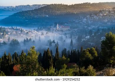 Beautiful view of morning cloud inversion in the Judean hills around Ein Karem neighborhood, biblical birth place of John the Baptist, with Catholic Church of Saint John the Baptist; Jerusalem Israel