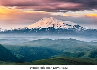 Beautiful view of mount Elbrus in the morning at sunrise with a dramatic cloudy sky and foggy green highland meadows. Summer mountain landscape. North Caucasus, Karachay-Cherkess Republic, Russia