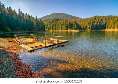 Beautiful view of the mountain lake Synevyr. Carpathians, Ukraine. Wooden raft on foreground. Most visited location of Carpathian mountains in Ukraine
