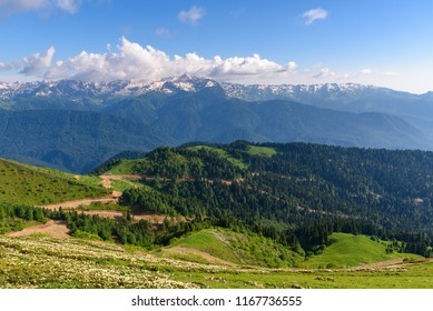 Beautiful view of the mountain range of the Caucasus Mountains from the top of the Rosa Peak, Sochi Russia. Mountain road serpentine going through the forest