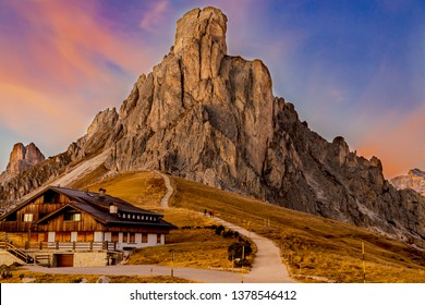 Beautiful view of the mountain range in the rays of the setting sun. Pink clouds in the blue sky. Yellow grass at the foot of the mountain. Mountain Refuge, road to the mountains, stairs