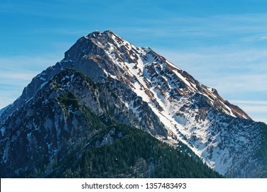 Beautiful view of mountain top with remnants of snow on slopes and coniferous forests below in Kamnik-Savinja Alps in Slovenia. Climbing, hiking, mountaineering, lifestyle and nature concepts.