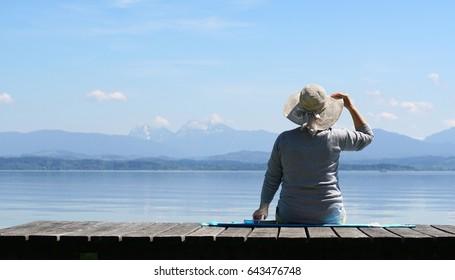 bellas vistas a las montañas, anciana con sombrero en un embarcadero de madera en el lago