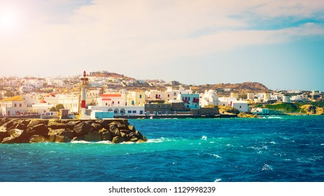 Beautiful view to Mykonos windmills and lighthouse from seaside