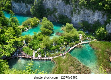 The beautiful view na the turquoise clear water of Plitvice lake. In this water live a any species of fish and birds. Over the water is a wooden footbridge for people to walk around.