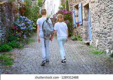 Beautiful view of narrow old street with historic traditional houses in old villge in Europe with blossom bushes of hydrangea. Teenagers people and travel concept. Teens walking