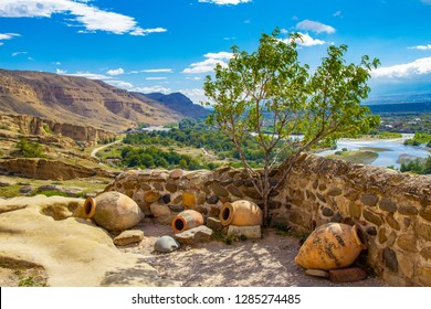 Beautiful view of the national pitcher and a Bush of olive-tree on background of the valley of the river Kura in antique cave city Uplistsikhe, near Gori, Shida Kartli, Georgia, in a Sunny sammer day,