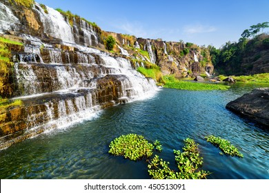 Beautiful view of natural cascading waterfall with crystal clear water and scenic pool among rocks in summer. Sunny landscape in Vietnam. The Pongour waterfall is a popular tourist destination of Asia