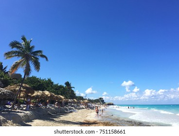 Beautiful view of the ocean. Waves, palm trees and white sand. Atlantic coast of Cuba. People on the beach