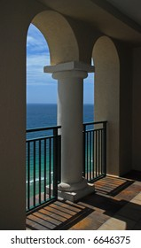 A beautiful view of the ocean and waves through the arches of a balcony.