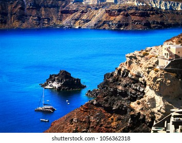 Beautiful view from Oia village, Santorini, Cyclades, Southern Greece. Beautiful scenery - colorful rugged volcanic rocks, little Saint Nicholas island, boats and brigh blue water of Aegean Sea