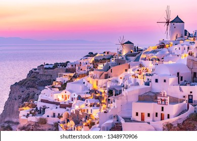 Beautiful view of Oia village with traditional white architecture and windmills in Santorini island in Aegean sea at sunset, Greece. Scenic travel background.