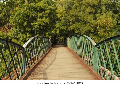 Beautiful view of old wood and iron bridge above some water. Gangway with green railings, leading to some park or forest with green trees and bushes. Shadow of the bars on wooden footbridge. Summer.