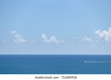 Beautiful view on Atlantic ocean. Small boat in the sea. Summer vacations destination. Traveling. Sky, sea and clouds,