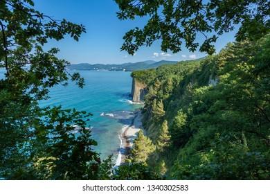 Beautiful view on blue sea landscape, green summer trees near kiselev rock Tuapse. Russia