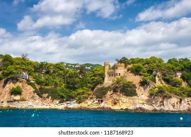 Beautiful view on Castell d'en Plaja from seaside in Lloret de Mar, Costa Brava, Spain. Sunny summer day in Lloret de Mar. Rocky coastline in spanish beach