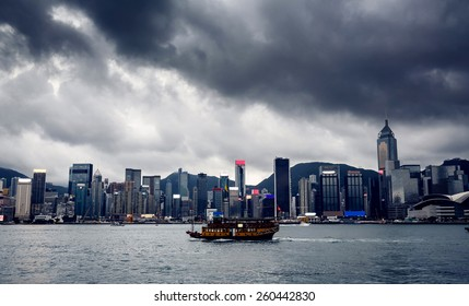 Beautiful view on Hong Kong city buildings and river with yacht with cloudy sky on background