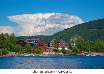 Beautiful view on the promenade, traditional houses and Ferris Wheel over the lake Titisee against amazing cloudy sky. Black Forest national park, Germany.