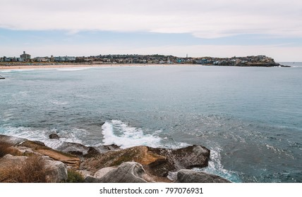 Beautiful view on the Sydney Bondi beach bay with surfers swimming in the waves and cliffs around the bay