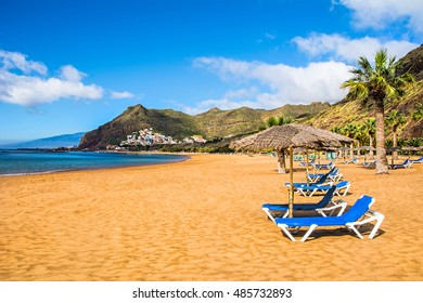 Beautiful view on Teresitas beach near Santa Cruz de Tenerife with palms, yellow sand and deck chairs in a hot afternoon. Location: Teresitas beach, Santa Cruz, Tenerife, Canary Islands, Spain.