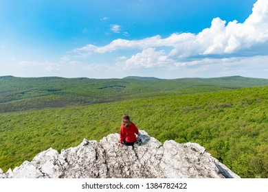 Beautiful view on vast green forest. Studeny hrad in mountain Tribec close to castle Gymes. Healthy green planet Earth. Person sitting on rock and enjoying view on deciduous forest or greenwood. - Shutterstock ID 1384782422