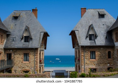 Beautiful view on the white sand beach and blue sea through two mirror like historic stone houses on sunny day with cloudless sky in Perros Guirec, Brittany, France