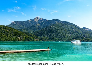 Beautiful view on Wolfgangsee lake by in St Sankt Gilgen with alps mountains, boats, Sailboats, blue sky, clouds, Schafberg mountain, ship.  Salzkammergut, Salzburg, Austria