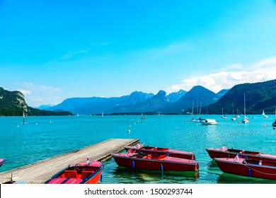 Beautiful view on Wolfgangsee lake by in St Sankt Gilgen with alps mountains, boats, sailboats, blue sky, clouds. Salzkammergut, Salzburg, Austria