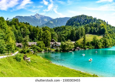 Beautiful view on Wolfgangsee lake by in St Sankt Gilgen with alps mountains, boats, sailboat, sailboats, Schafberg mountain, blue sky, clouds. Salzkammergut, Salzburg, Austria