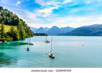 Beautiful view on Wolfgangsee lake by in St Sankt Gilgen with alps mountains, boats, sailboat, sailboats, blue sky, clouds. Salzkammergut, Salzburg, Austria