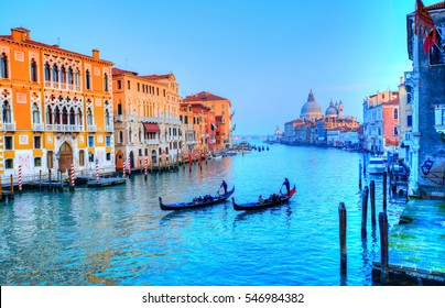 Beautiful view over the famous Grand Canal illuminated in sunset light, and gondolier transporting tourists with gondola, in Venice - Italy