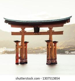 """Beautiful view over famous Itsukushima Shrine on Miyajima Island in Japan at high tide during sunset. Translation of text on the Shrine """"Itsukushima Shrine""""."""