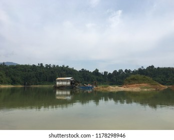 Beautiful view over lake area. there is a hill in the background and there are green forests around. There are floating houses and boats on the water. there is a small island in the middle.