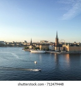 Beautiful view over Swedish capital on a summer evening. Blue water, blue sky, Buildings, boats and churches in the sunset.