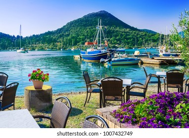 Beautiful view over terrace near the beach with flowers on table in Nydri village, seaport of Lefkada, in Greece