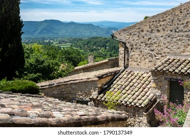 Beautiful view over tiles roofs at the french hilltop Mirmande village and the Rhone valley on the background.