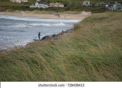 Beautiful view overlooking sand dune grass on beach coast with luxury summer homes and surfers in the distance background