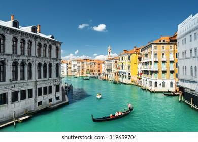 Beautiful view of the Palazzo dei Camerlenghi (Fondamenta de la Preson) and the Grand Canal with gondolas from the Rialto Bridge in Venice, Italy. Venice is a popular tourist destination of Europe.