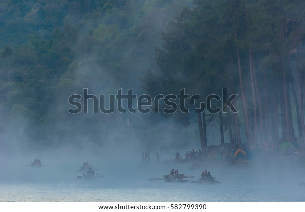 Beautiful view of People on Bamboo Boat with Fog in Lake and Pine Tree Background