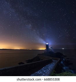 """Beautiful view of """"Phare du Petit Minou"""" on a wonderful cloudless night with light on and milky way on the background."""
